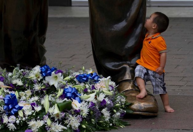 A child looks up at a giant bronze statue of former president Nelson Mandela, on Mandela Square in Sandton, Johannesburg, Friday, Dec 6.2013.Photo- Athol Moralee.