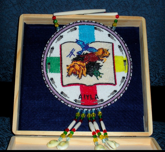 Award medallion Seal designed by Corwin Clairmont (Salish) Beaded by Linda King (Salish). Flickr- htomren.