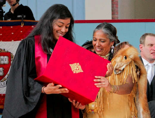 Smalley and Cheryl Andrews-Maltais, chairwoman of the Wampanoag Tribe accept a posthumous degree from the university in the honor of another Aquinnah Wampanoag, Joel Iacoomes, who died in 1665. Photo- Ivyashe.