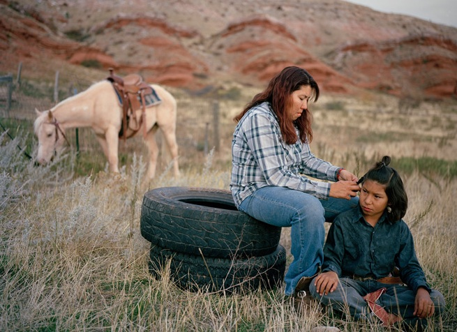 On the Crow Reservation in southern Montana, Michelle Walking Bear braids her 11-year-old son's hair to keep it out of his face when he rides. Photo by Erika Larsen.