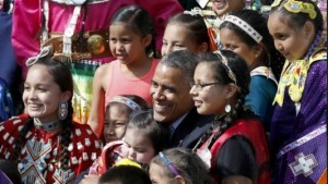 President Barack Obama poses with Native American dancers and children during his visit to the Standing Rock Indian Reservation Friday, June 13, 2014, photo in Cannon Ball, N.D. Credit- Philly News.