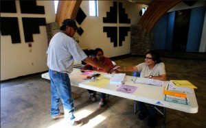 Poll workers Briana Ashley and Marlene Gonzalez help a voter on Tuesday, July 21, 2015, at Nenahnezad Chapter House.