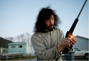 Peter Paul Kawagaelg Williams, the founder of Shaman Furs, performs a smudging ceremony for his hunting rifle outside his home in Sitka, Alaska. Credit James Poulson for The New York Times.